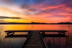 brown wooden dock on lake during sunset