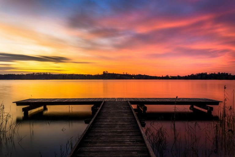 brown wooden dock on lake during sunset